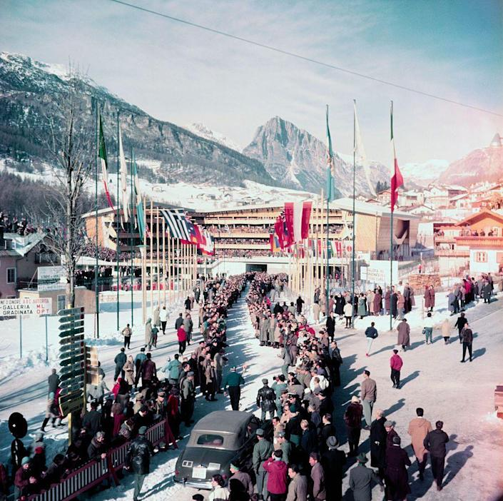 <p>The Olympics stadium at the 1956 Winter Olympics had been temporarily expanded to house 14,000 spectators to view the opening ceremonies. The event was also broadcast on television — a fact that led to a surprising mishap during the torch relay. While speed skater Guido Caroli made a lap around the stadium, he tripped over a TV cable and fell. Luckily, he regained his footing and was able to light the cauldron. </p>