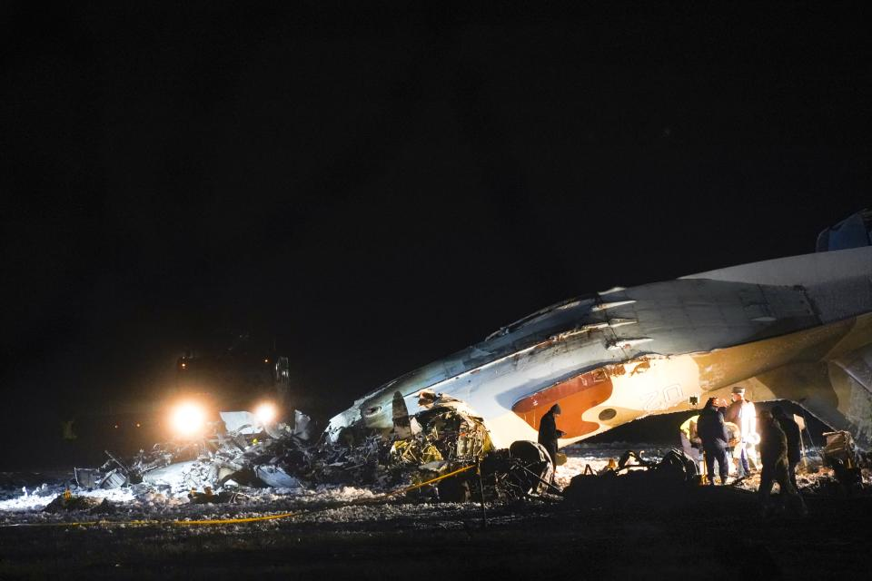 Emergency employees work at the side of the crashed Soviet-built An-26 two-engine turboprop at the airport of Kazakhstan's largest city, Almaty, Kazakhstan, Saturday, March 13, 2021. Officials in Kazakhstan say a plane operated by the country's state security agency has crashed, killing four crew members and injuring the other two. The Emergencies Ministry said the Soviet-built An-26 two-engine turboprop crashed while trying to land Saturday at the airport of Kazakhstan's largest city, Almaty. (AP Photo/Vladimir Tretyakov)