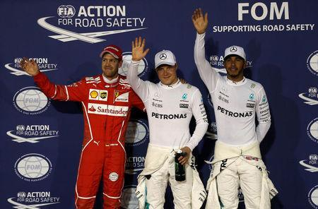 Formula One - F1 - Bahrain Grand Prix - Sakhir, Bahrain - 15/04/17 - Ferrari Formula One driver Sebastian Vettel of Germany, Mercedes Formula One driver Valtteri Bottas of Finland and Mercedes Formula One driver Lewis Hamilton of Britain celebrate on the podium after taking pole position following the qualifying session. REUTERS/Hamad I Mohammed