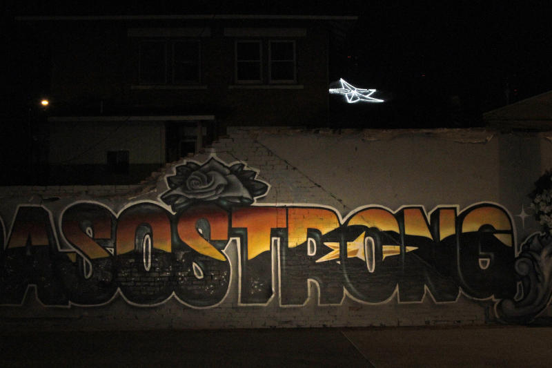 """In this May 7, 2020, photo, an """"El Paso Strong"""" mural is seen at night in El Paso, Texas. Gabe Vasquez and Justin Martinez painted the mural in August after the mass shooting at a Walmart on that killed 23 people. The star painted in the mural's letters can be seen in the background on the southern slope of the Franklin Mountains. (AP Photo/Cedar Attanasio)"""
