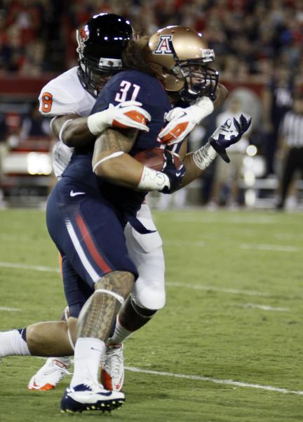 Arizona's Taimi Tutogi (31) is tackled by Oregon State's Tyrequek Zimmerman (8) during the first quarter of an NCAA college football game at Arizona Stadium in Tucson, Ariz., Saturday, Sept. 29, 2012. (AP Photo/Wily Low)