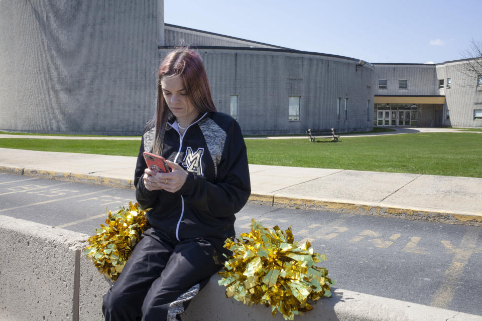 FILE - In this April 4, 2021, file photo provided by the American Civil Liberties Union, Brandi Levy wears her cheerleading outfit as she looks at her mobile phone outside Mahanoy Area High School in Mahanoy City, Pa. The Supreme Court ruled Wednesday, June 23, 2021, that the public school wrongly suspended Levy from cheerleading over a vulgar social media post she made after she didn't qualify for the varsity team. (Danna Singer/ACLU via AP, File)