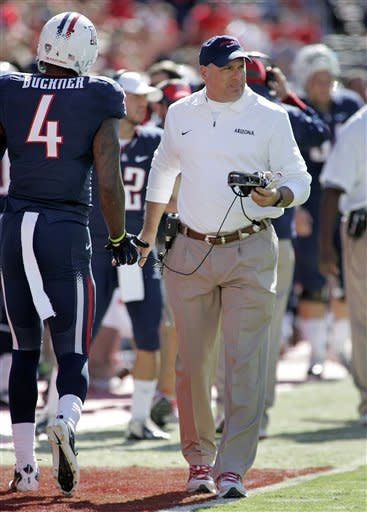 Arizona head coach Rich Rodriguez, right, exchanges handshakes with Dan Bucker (4) on the sidelines during the first half of an NCAA college football game against Colorado at Arizona Stadium in Tucson, Ariz., Saturday, Nov. 10, 2012. (AP Photo/John Miller)