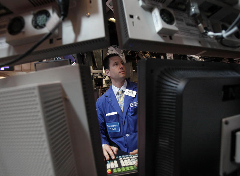 FILE- In this May 17, 2012 file photo specialist Stephen D'Agostino works at his post on the floor of the New York Stock Exchange. The U.S. corporate earnings season resumes in earnest the week of Monday, July 16, 2012, with reports from major companies that cover a wide span of the economy. On deck Tuesday are Harley-Davidson, Coca-Cola, Goldman Sachs and Johnson & Johnson. Intel and Yahoo also report this week.  (AP Photo/Richard Drew)