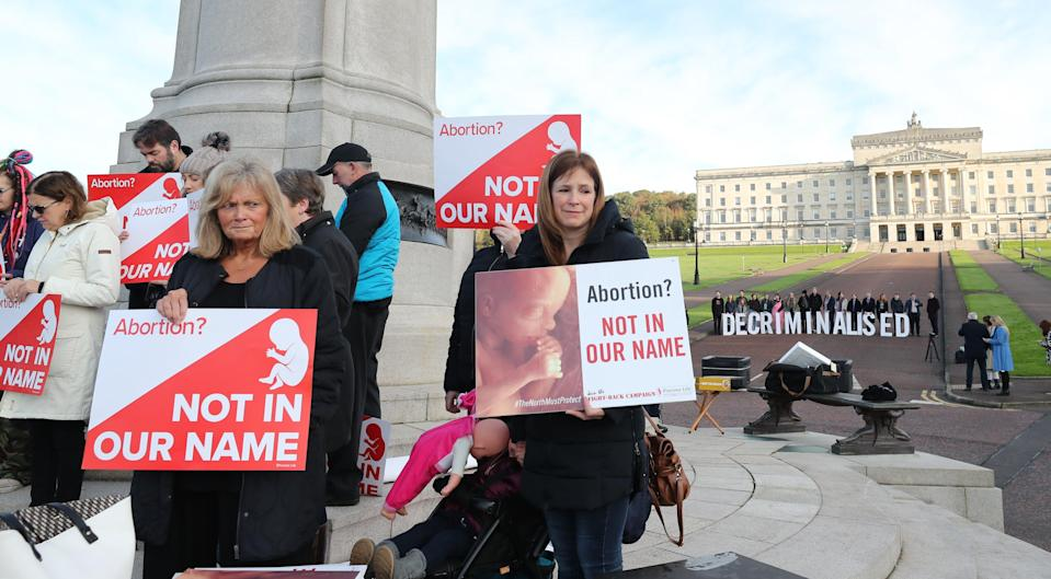 Anti-abortion and pro-choice activists take part in separate protests at Stormont (Niall Carson/PA) (PA Archive)