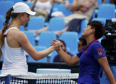 Mona Barthel (L) of Germany shakes hands with Luksika Kumkhum of Thailand after winning their women's singles match at the Australian Open 2014 tennis tournament in Melbourne January 15, 2014. REUTERS/David Gray