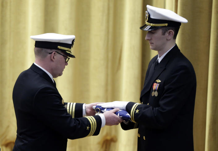 """Commander Rolf Spelker, left, receives the commission pennant at the decommissioning ceremony for the fire-damaged USS Miami nuclear submarine at the Portsmouth Naval Shipyard, Friday, March 28, 2014, in Kittery, Maine. Rear Adm. Ken Perry, commander of the submarine Group Two in Groton, Conn., where the sub was based, acknowledged the seriousness of the event, but told the crowd they were there to celebrate the submarine and its crew's achievements. """"This is a tribute. This is a celebration of the ship's performance and the superb contributions to the nation's defense and this is how we're going to treat it. So I expect to see some smiles out there,"""" he said. (AP Photo/Robert F. Bukaty)"""