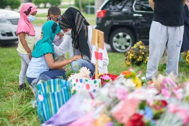 Mourners gather at a memorial for the four victims of a Sunday hit-and-run in London, Ont., which police say was a targeted attack against a Muslim family. (Geoff Robins/The Canadian Press - image credit)