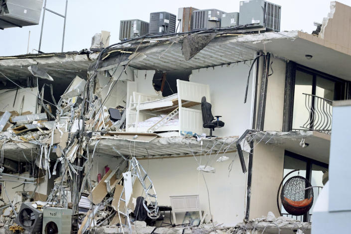 Debris dangles from Champlain Towers South Condo after the multistory building partially collapsed Thursday, June 24, 2021, in Surfside, Fla. (David Santiago /Miami Herald via AP)