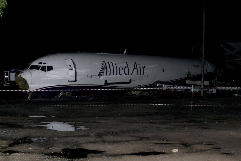 The wreckage of a Boeing 727 cargo plane sits cordoned off on a roadway near Kotoka International Airport in Accra, Ghana, Saturday, June 2, 2012. The cargo plane attempting to land at the airport Saturday, slamming into a bus loaded with passengers on a nearby street, killing all 10 people inside the vehicle, emergency responders and airport officials said. (AP Photo/Christian Thompson)
