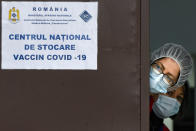 In this photo taken on Friday, Dec. 18, 2020 medical staff wearing masks for protection against the COVID-19 infection peer from behind a door at the National Center for Storage of the COVID-19 Vaccine, a military run facility, in Bucharest, Romania. Across the Balkans and the rest of the nations in the southeastern corner of Europe, a vaccination campaign against the coronavirus is overshadowed by heated political debates or conspiracy theories that threaten to thwart the process. In countries like the Czech Republic, Serbia, Bosnia, Romania and Bulgaria, skeptics have ranged from former presidents to top athletes and doctors. Nations that once routinely went through mass inoculations under Communist leaders are deeply split over whether to take the vaccines at all. (AP Photo/Andreea Alexandru)