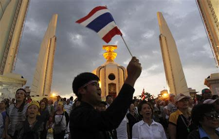 A protester waves a Thai national flag as he joins others in a rally at the Democracy Monument in Bangkok