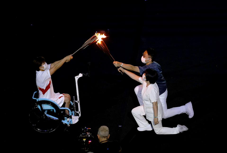 <p>TOKYO, JAPAN - JULY 23: The torch carriers exchange the flame of the Olympic torch during the Opening Ceremony of the Tokyo 2020 Olympic Games at Olympic Stadium on July 23, 2021 in Tokyo, Japan. (Photo by Laurence Griffiths/Getty Images)</p>