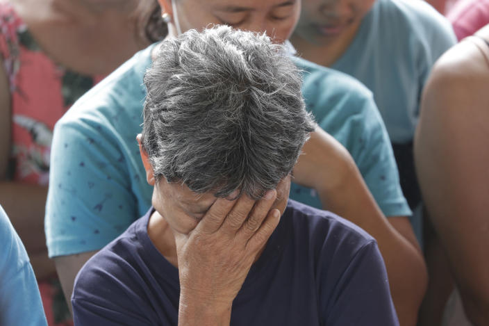 A woman reacts during prayers before the distribution of relief goods at an evacuation center at Santa Teresita, Batangas province, southern Philippines on Thursday Jan. 16, 2020. Taal volcano belched smaller plumes of ash Thursday but shuddered continuously with earthquakes and cracked roads in nearby towns, which were blockaded by police due to fears of a bigger eruption. (AP Photo/Aaron Favila)