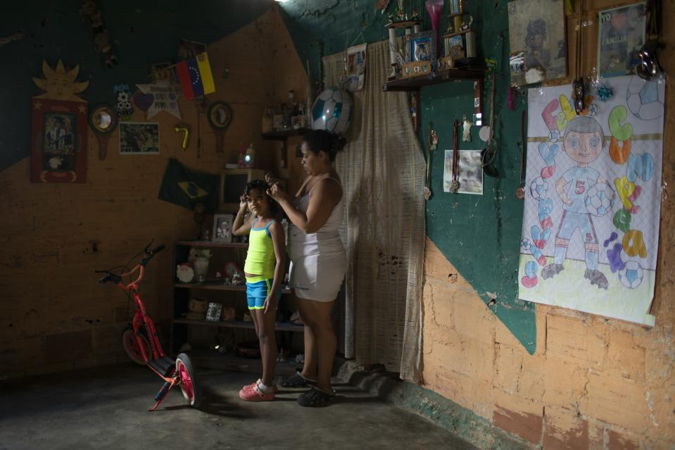 Yangervis Blanco, 7, stands still as her mother helps her prepare for a homespun beauty pageant in the Antimano neighborhood of Caracas, Venezuela, Friday, Feb. 5, 2021. Neighbors in the hillside barrio gathered for the carnival pageant tradition to select their child queen for the upcoming festivities. (AP Photo/Ariana Cubillos)