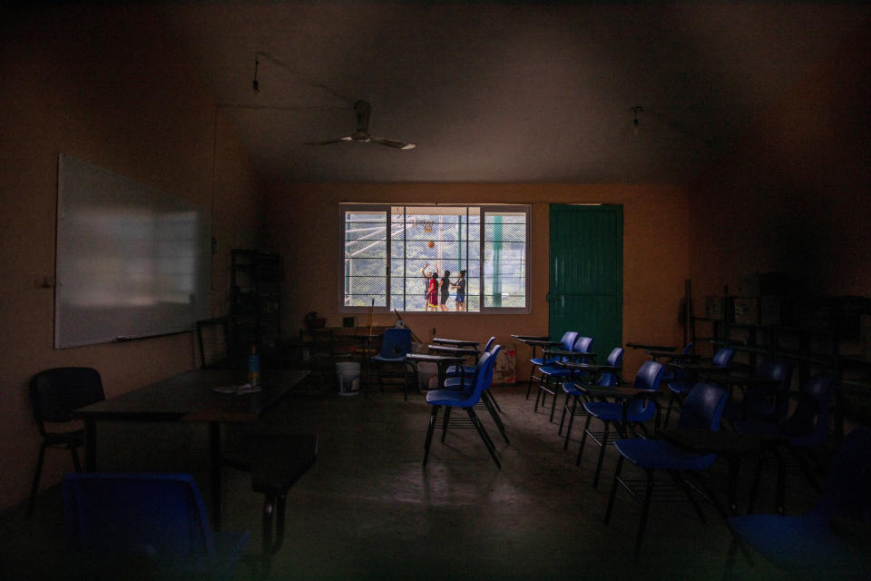 A classroom sits empty at La Ilusion community school, closed amid the COVID-19 pandemic, where girls play basketball outside in La Ilusion, Chiapas state, Mexico, Wednesday, Sept. 19, 2020. Amid the new coronavirus pandemic, Mexican education officials recently said that enrollment for the new school year was down about 10%, but some teachers warn that many students enrolled out of habit, but aren't participating. (AP Photo/Eduardo Verdugo)