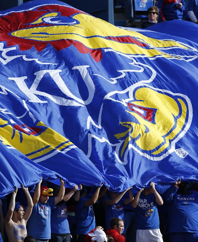 Kansas fans wave a banner during the second half of an NCAA college football game against West Virginia at Kansas Memorial Stadium in Lawrence, Kan., Saturday, Nov. 16, 2013. Kansas defeated West Virginia 31-19. (AP Photo/Orlin Wagner)