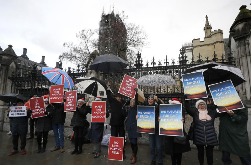 Pro Brexit demonstrators celebrate outside Parliament in London, Friday, Dec. 20, 2019. Members of the British parliament on Friday voted to approve in principle Prime Minister Boris Johnson's Brexit bill, paving the way for Britain to leave the EU next month. (AP Photo/Kirsty Wigglesworth)