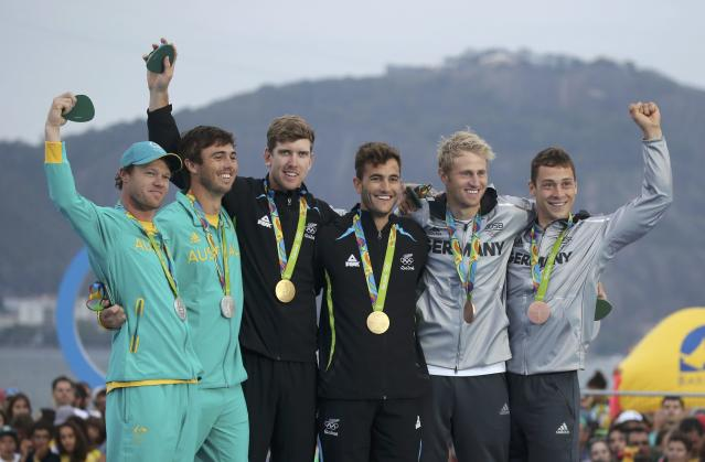 2016 Rio Olympics - Sailing - Victory Ceremony - Men's Skiff - 49er Victory Ceremony - Marina de Gloria - Rio de Janeiro, Brazil -18/08/2016. Nathan Outteridge (AUS) of Australia and Iain Jensen (AUS) of Australia, Peter Burling (NZL) of New Zealand and Blair Tuke (NZL) of New Zealand and Erik Heil (GER) of Germany and Thomas Ploessel (GER) of Germany celebrate on podium. REUTERS/Benoit Tessier FOR EDITORIAL USE ONLY. NOT FOR SALE FOR MARKETING OR ADVERTISING CAMPAIGNS.