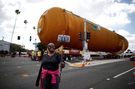 Eddye Chapman takes a picture of herself as the space shuttle Endeavour's external fuel tank ET-94 makes its way to the California Science Center in Exposition Park in Los Angeles, California, U.S. May 21, 2016. REUTERS/Lucy Nicholson