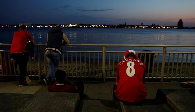 Soccer Football - Liverpool fans watch the Champions League Final - Liverpool, Britain - May 26, 2018 Liverpool fans look dejected after losing the final as they sit beside the river Mersey near Albert Dock REUTERS/Peter Nicholls TPX IMAGES OF THE DAY