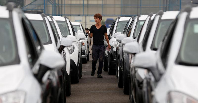 FILE PHOTO: A worker checks cars made by GM Korea in a yard of GM Korea's Bupyeong plant in Incheon
