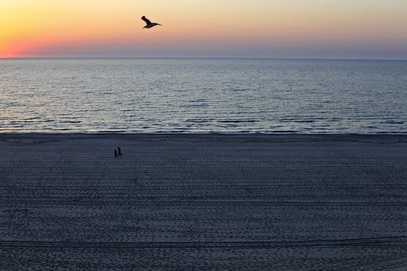 People stroll on the beach at the dawn in the Black Sea resort of Mamaia