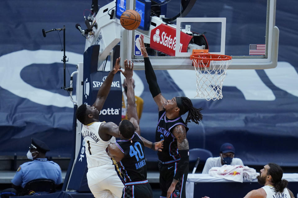New Orleans Pelicans forward Zion Williamson (1) goes in for a layup against Sacramento Kings forward Harrison Barnes (40) and center Richaun Holmes in the first half of an NBA basketball game in New Orleans, Monday, April 12, 2021. (AP Photo/Gerald Herbert)