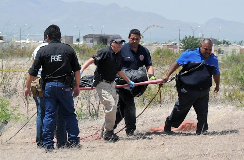 Police and forensic personnel carry the body of Cristopher Raymundo Marquez Mora in Chihuahua on May 16, 2015 (AFP Photo/Daniel Acosta)