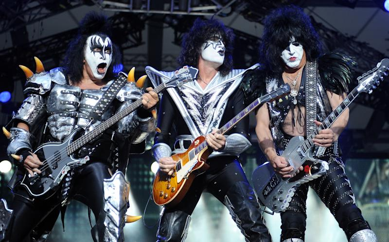 FILE - In this June 13, 2013, file photo, from left, bassist Gene Simmons , guitarist Tommy Thayer and singer Paul Stanley of the US band Kiss perform on stage in Berlin, Germany. Kiss and Def Leppard are joining forces for a summer tour. The legendary bands will embark on a U.S. tour June 23 in West Valley City, Utah. (AP Photo/dpa,Britta Pedersen, File)