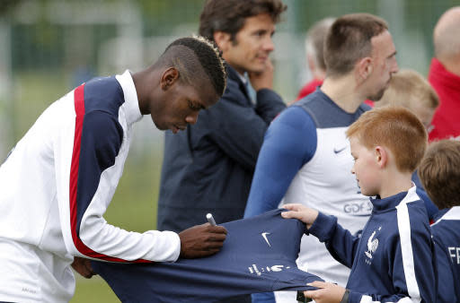 In this Friday, May 23, 2014 file photo, France's soccer player Paul Pogba signs an autograph before a training session at the Clairefontaine training center, outside Paris. Not all the money that will change hands after the World Cup, when clubs trade players who distinguish themselves on footballs biggest stage, will line the pockets of selling clubs, agents and the players themselves. A sliver of the wealth will also trickle down to footballs grassroots, to unpretentious, volunteer-run clubs where kids take first steps toward their dreams of making a career in the sport. (AP Photo/Christophe Ena, File)