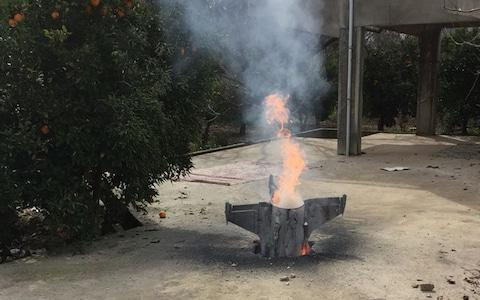 Flames rise from a missile, which according to the Lebanon national news agency appears to be part of a Syrian air defense missile targeting an Israeli warplane which landed in a lemon grove, in Hasbani village, southwest Lebanon - Credit: AP