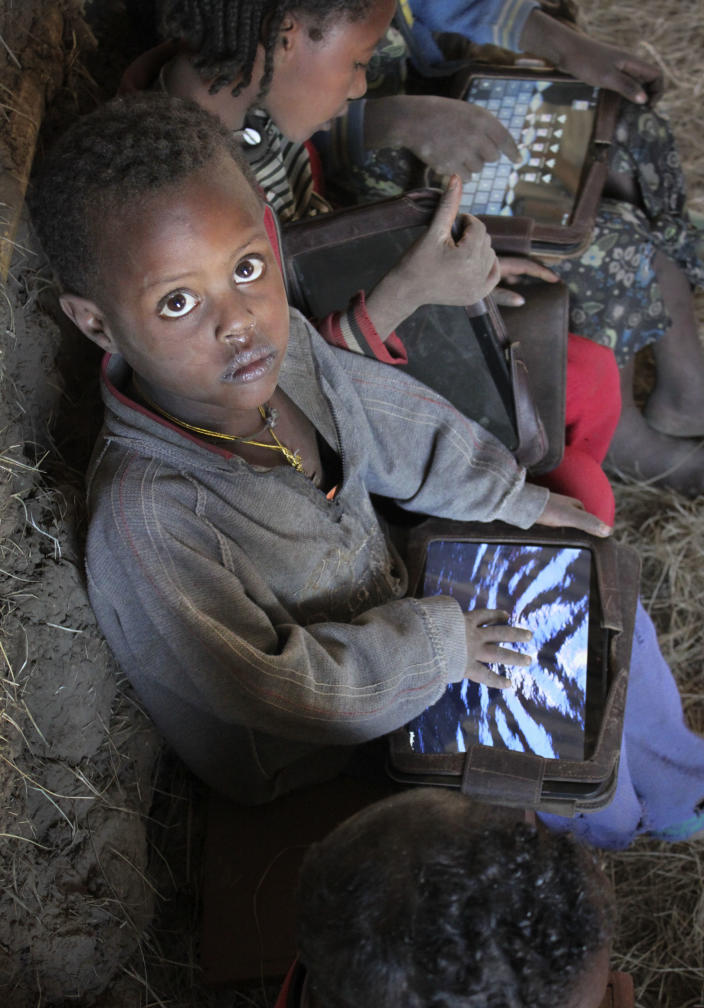 In this photo taken Tuesday, Nov. 27, 2012, a boy sits among children using tablet computers given to them by the One Laptop Per Child project in the village of Wenchi, Ethiopia. The project gave tablets to the children in the poor, illiterate village to see how much the children could teach themselves and now many kids can recite the English alphabet and spell words in English. (AP Photo/Jason Straziuso)