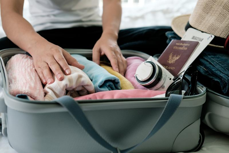 Midsection Of Woman Packing Suitcase On Bed