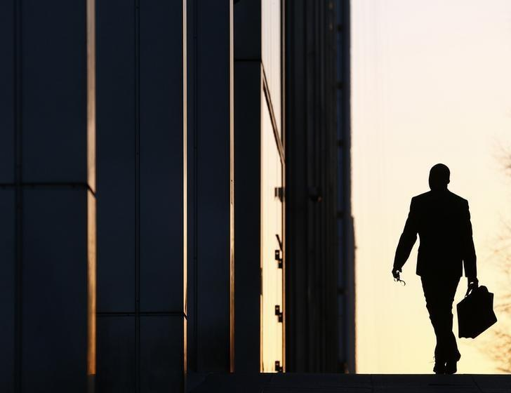 A worker arrives at his office in the Canary Wharf business district in London February 26, 2014. REUTERS/Eddie Keogh/Files