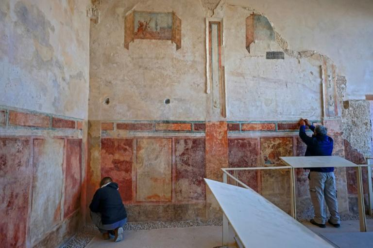 Specialists from the Israel Antiquities Authority restore an ancient wall painting in Herod's palace-fortress