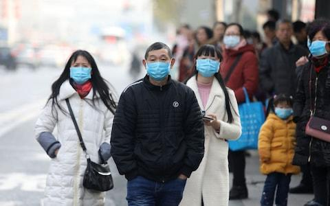 Chinese residents wear masks while waiting at a bus station - Credit: Rex