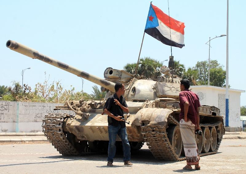 Yemeni supporters of the southern separatist movement stand next to a tank bearing the movement's flag which they confiscated from a military depot, in the southern Yemeni city of Aden on March 27, 2015 (AFP Photo/Saleh al-Obeidi)