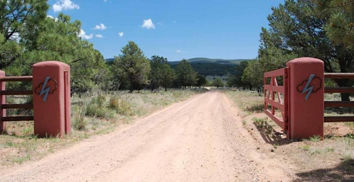 """<p>The gate to Forked Lightning Ranch, bearing the property's emblem. <i>(Photo: <a href=""""http://bit.ly/1oZ16Zz"""" rel=""""nofollow noopener"""" target=""""_blank"""" data-ylk=""""slk:Swan Land Company"""" class=""""link rapid-noclick-resp"""">Swan Land Company</a>)</i></p>"""