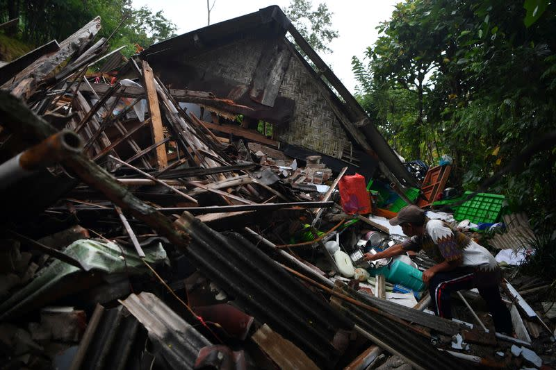 A man salvages his belongings at a house damaged by an earthquake in Lumajang