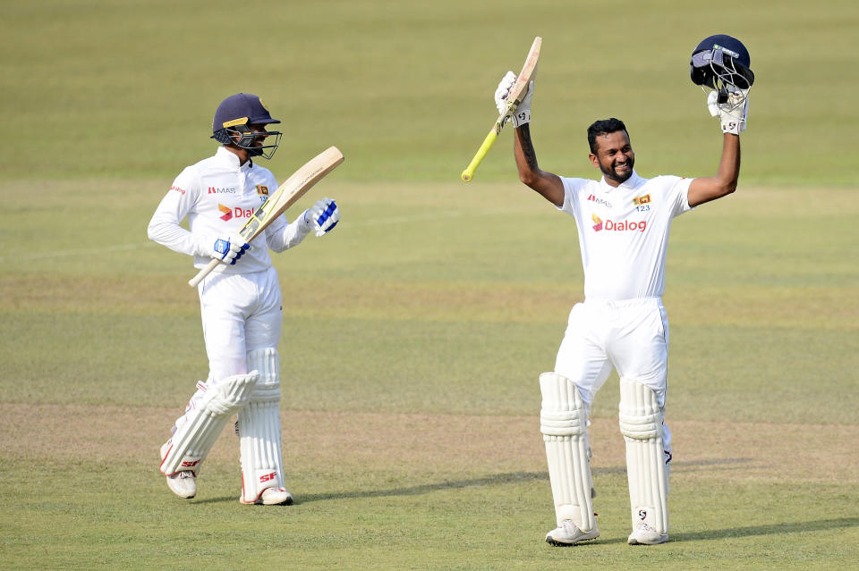 Sri Lanka batsman Dimuth Karunaratne, right, raises his bat as he celebrates scoring a double century as non-striker Dhanjaya De Silva, left, congratulates him during the fourth day of the first test cricket match between Sri Lanka and Bangladesh in Pallekele, Sri Lanka, Saturday, April 24, 2021.( AP Photo/Sameera Peiris)