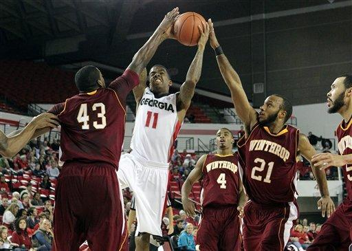 Georgia guard Vincent Williams, center, is blocked by Winthrop defenders (43) George Valentine, left, and (21) Andre Jones, right, as he drives to the basket during first half action of an NCAA college basketball game at Stegeman Coliseum in Athens, Ga on Tuesday, Dec. 27, 2011. (AP Photo/Atlanta Journal-Constitution, Curtis Compton)