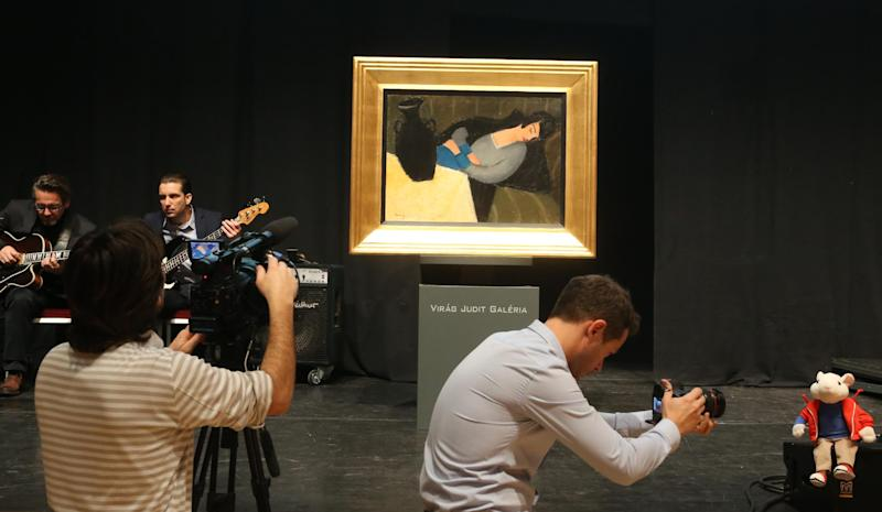 """The painting """"Sleeping woman with black vase"""" by Hungarian artist Robert Bereny and a plush figure of the """"Stuart Little"""" character seen prior to an auction of the painting at the Judit Virag Gallery in Budapest on December 13, 2014 (AFP Photo/Ferenc Isza)"""