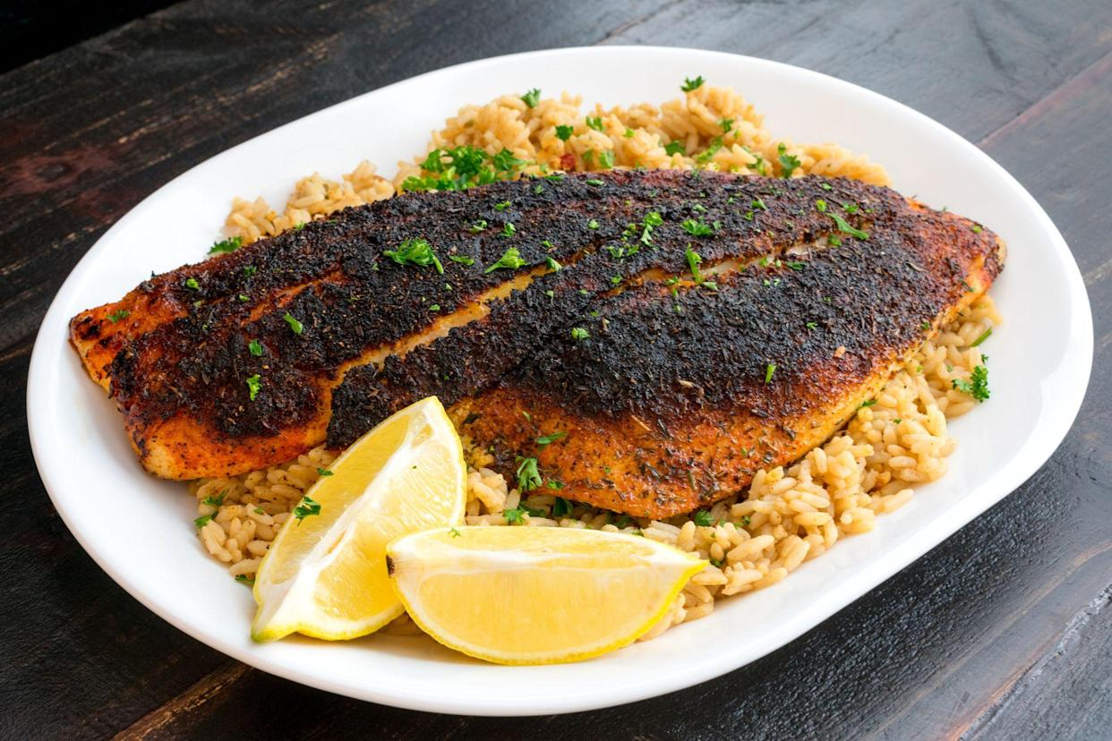 Blackened red snapper fillet served on a platter of dirty rice with lemon wedges and parsley garnish