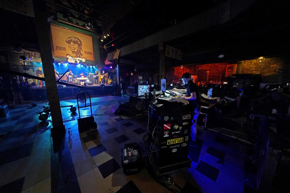 In this Oct. 26, 2020, photo, production engineers record the band Galactic for a video stream concert, inside an empty Tipitina's music club, which the band owns, in New Orleans. Music clubs all over the nation — pop culture icons like the Troubadour in West Hollywood, the Bluebird Cafe in Nashville, The Bitter End in New York's Greenwich Village — are shuttered due to the coronavirus. And owners fear for the future of their businesses and of a musical way of life. (AP Photo/Gerald Herbert)