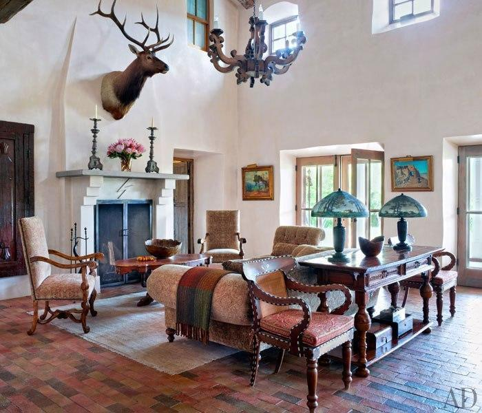 """<p>Presiding over the River House living room is an elk that Jane Fonda killed while hunting at Ted Turner's Flying D Ranch in Montana. The fireplace surround bears the Forked Lightning Ranch symbol. <a href=""""http://archdg.st/1oYTZR3"""" rel=""""nofollow noopener"""" target=""""_blank"""" data-ylk=""""slk:Click here to read more about Jane Fonda's ranch"""" class=""""link rapid-noclick-resp"""">Click here to read more about Jane Fonda's ranch</a> on ArchitecturalDigest.com, and <a href=""""http://archdg.st/1oZ5IPj"""" rel=""""nofollow noopener"""" target=""""_blank"""" data-ylk=""""slk:click here to see more pictures on AD's site"""" class=""""link rapid-noclick-resp"""">click here to see more pictures on AD's site</a>. <i>(Photo: Simon Upton/Architectural Digest)</i> <br></p>"""