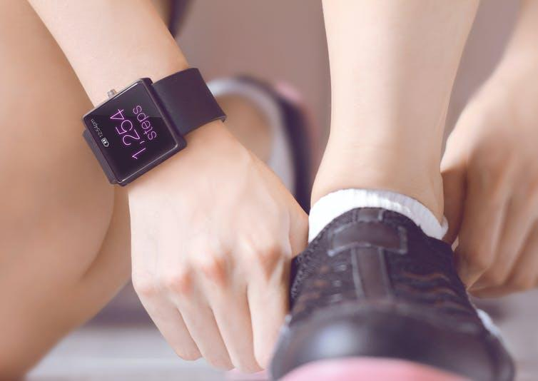 Person wearing a smartwatch tying their shoe.
