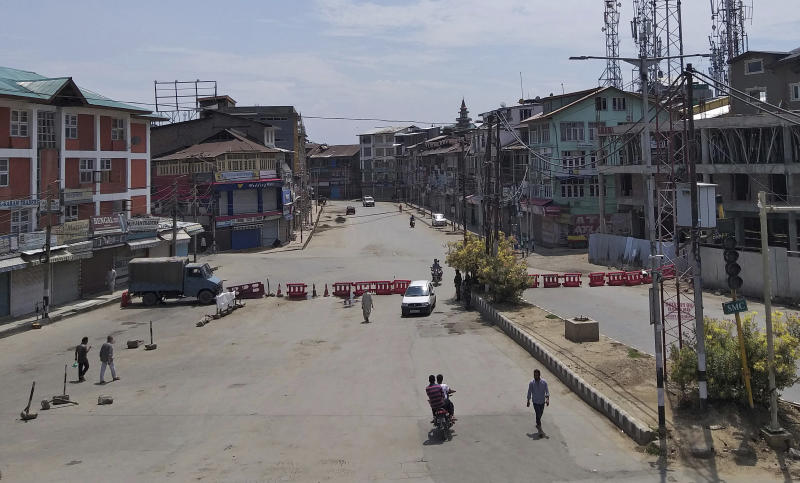 Pedestrians move on a deserted street in Srinagar, Indian controlled Kashmir, Thursday, Aug. 8, 2019. The lives of millions in India's only Muslim-majority region have been upended since the latest, and most serious, crackdown followed a decision by New Delhi to revoke the special status of Jammu and Kashmir and downgrade the Himalayan region from statehood to a territory. Kashmir is claimed in full by both India and Pakistan, and rebels have been fighting Indian rule in the portion it administers for decades. (AP Photo/Sheikh Saaliq)