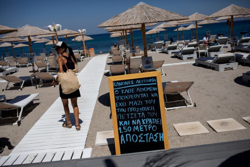 FILE PHOTO: A woman walks past an announcement calling for customers to maintain social distancing at a beach bar, following the coronavirus disease (COVID-19) outbreak, on the island of Kos