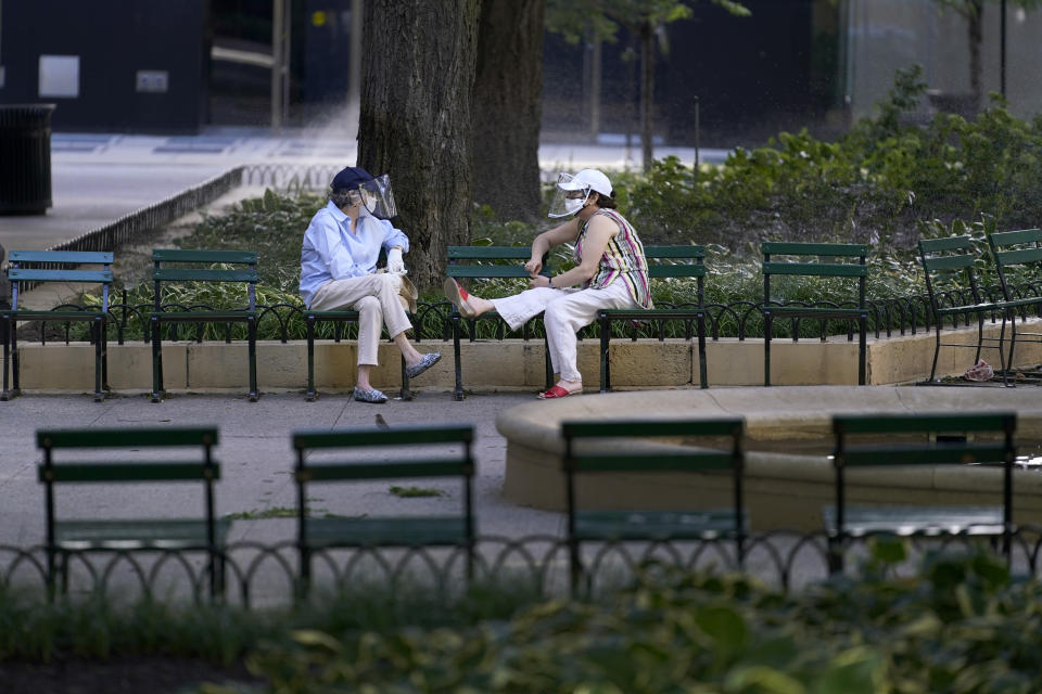 Two women wearing protective masks and face shields talk in a small park around the historic Water Tower on Chicago's Magnificent Mile on Tuesday, Aug. 11, 2019. (AP Photo/Charles Rex Arbogast)